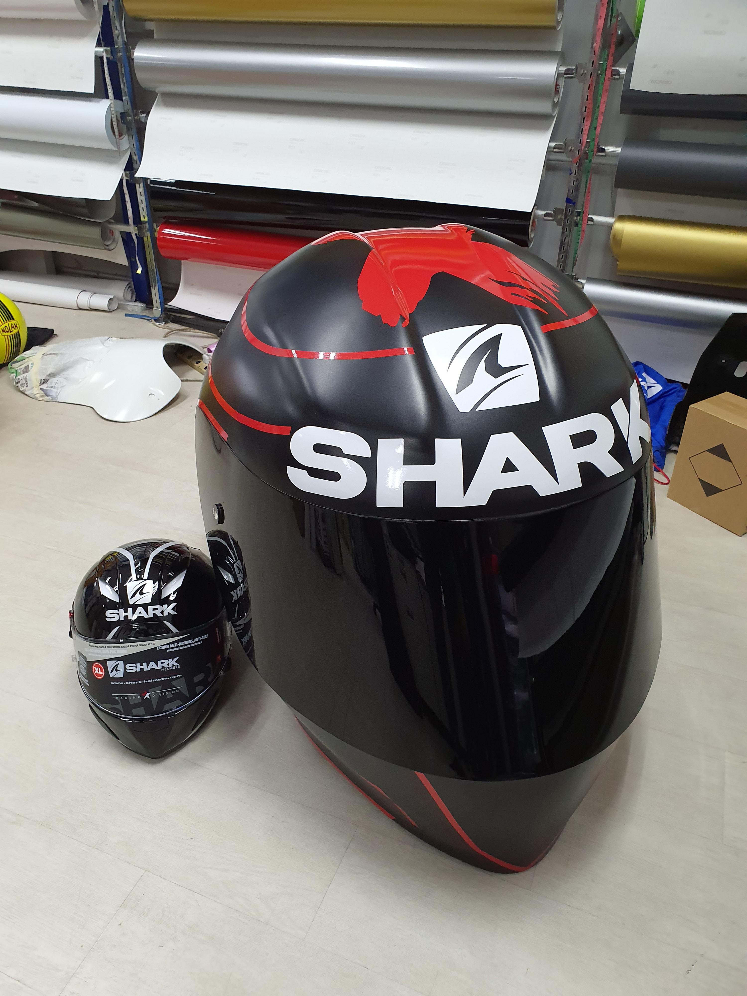 Gigantic Shark Helmet beside a normal helmet! It is at least 8 times bigger!